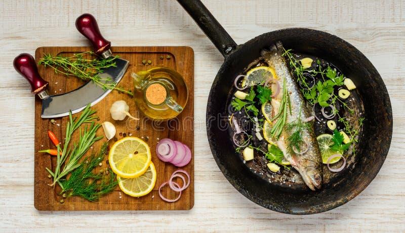 Fisk i stekpanna- och matlagningingredienser arkivbild