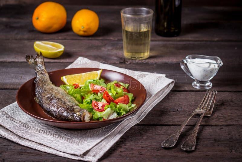 Fisk med sallad och vitt vin royaltyfri bild