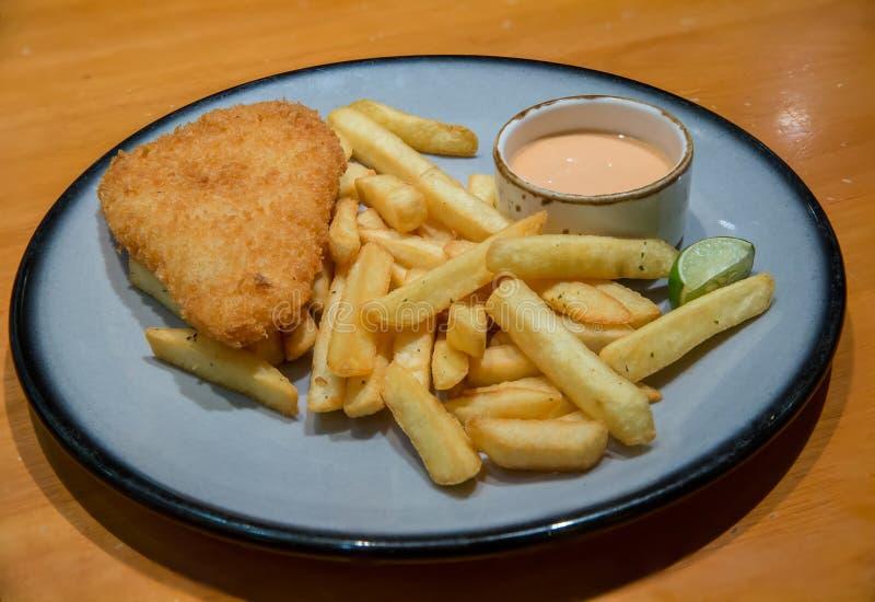 fisk och chiper med franska sm?fiskar - sjuklig mat Delen av den frasiga br?ade fiskfil?n med fransmansm?fiskar tj?nade som p? pl arkivfoto