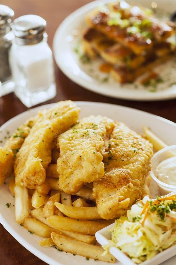 Fisk och chiper med räkarostat bröd arkivfoton