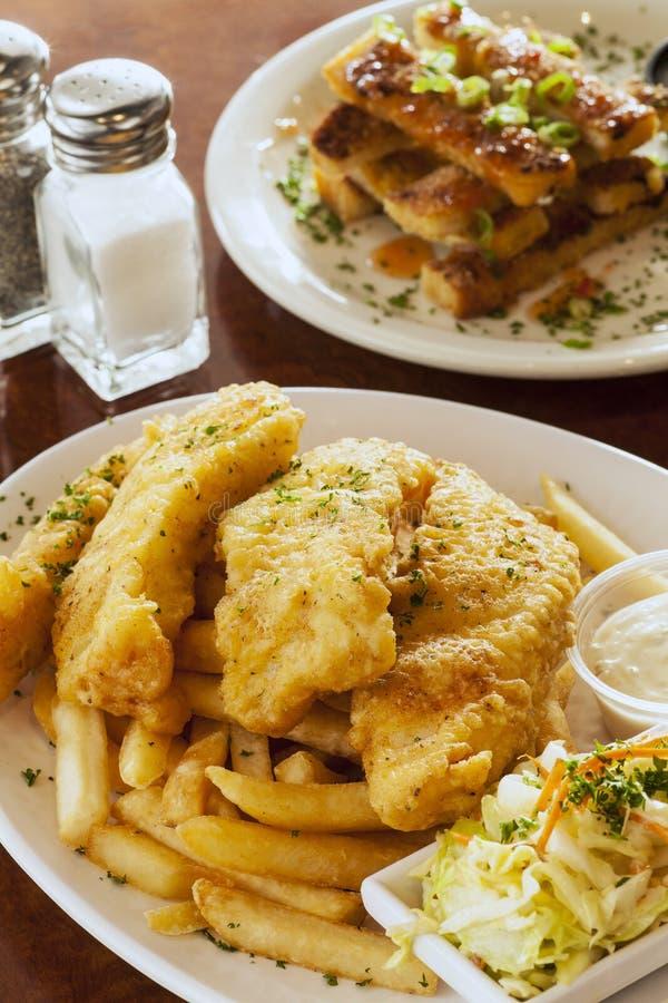 Fisk och chiper med räkarostat bröd royaltyfria bilder