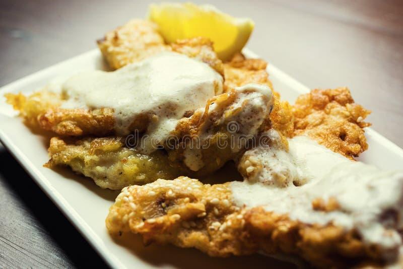 Fisk som stekas i smet, läcker slagen fisk på en platta med chiper, fisk och chipmål royaltyfria foton