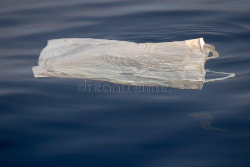 Fisk under plastpåsen i havet royaltyfri bild