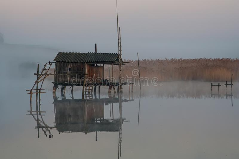 Fiska huset på vattnet i morgonen fördunkla royaltyfri bild