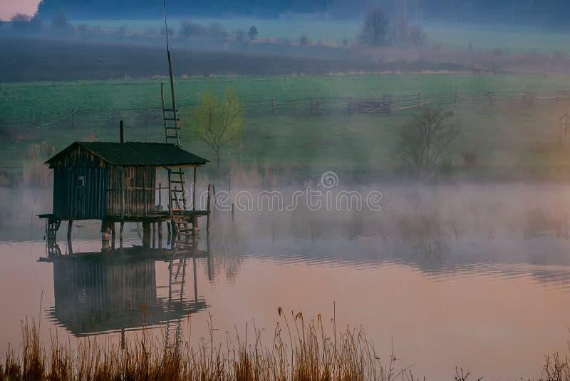 Fiska huset på vattnet i morgonen fördunkla royaltyfri fotografi