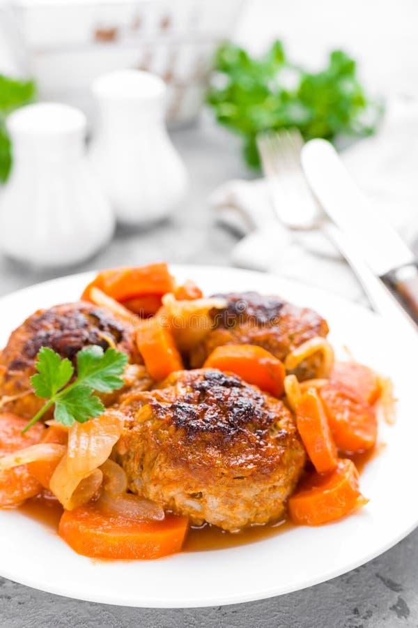 Fiska köttbullar eller noisettes som bakas med morot-, lök- och tomatsås Fiskköttbullar på plattan arkivbild