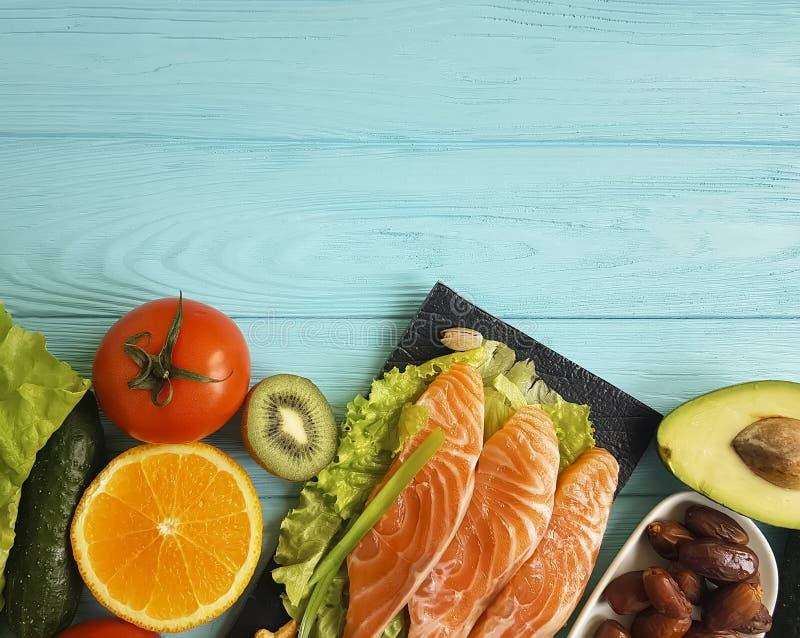 Fiska laxen som äter den vård- produkten för matställen på en olik blå träbakgrund royaltyfria foton