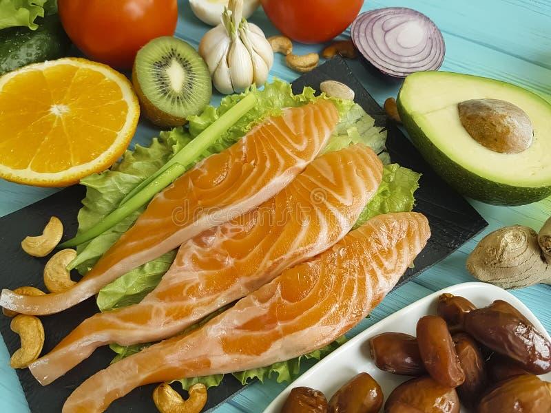 Fiska laxen som äter matställen på en olik blå träbakgrund arkivfoton