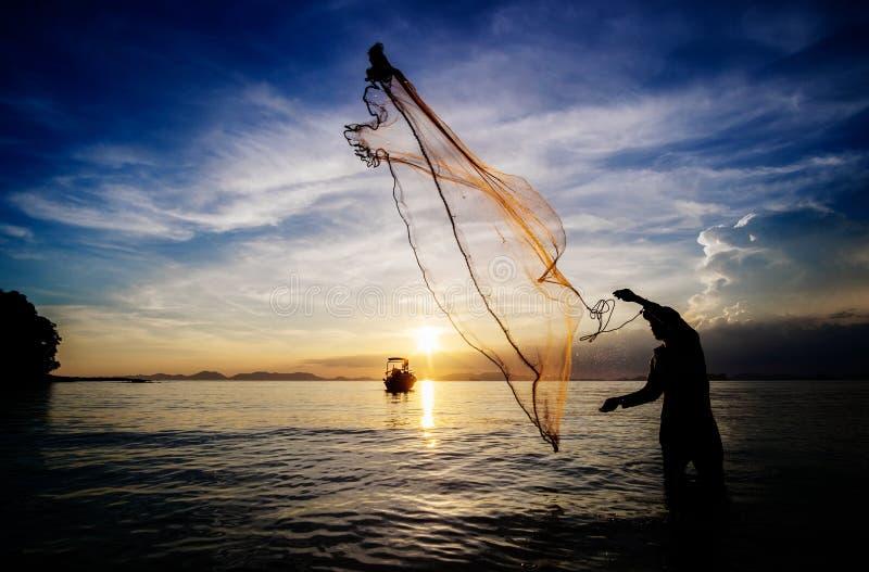 Fiska med netto på havet på ett lågvatten på solnedgången silhouette fotografering för bildbyråer
