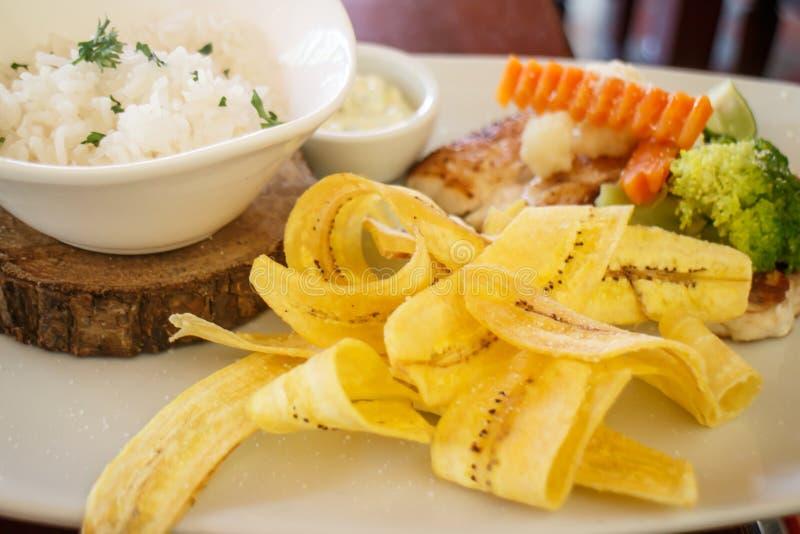 Fiska med ris och grönsaker och bananchiper royaltyfri foto