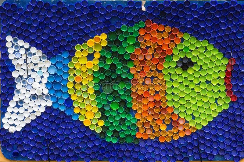 Fiska mosaikdeocorationen som göras av cororful plast- kapsyler S royaltyfria bilder