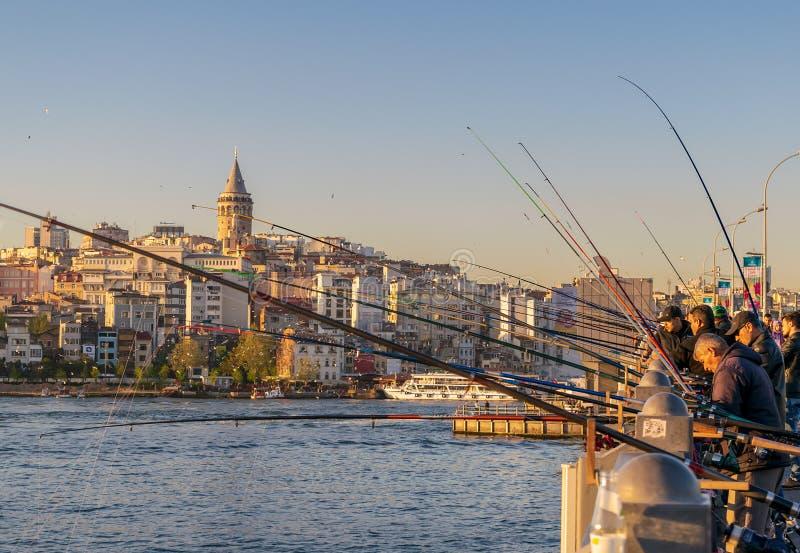 Fiska på det guld- hornet på den Galata bron för solnedgång med det Galata tornet i bakgrunden, Eminonu område, Istanbul, Turkiet royaltyfri fotografi