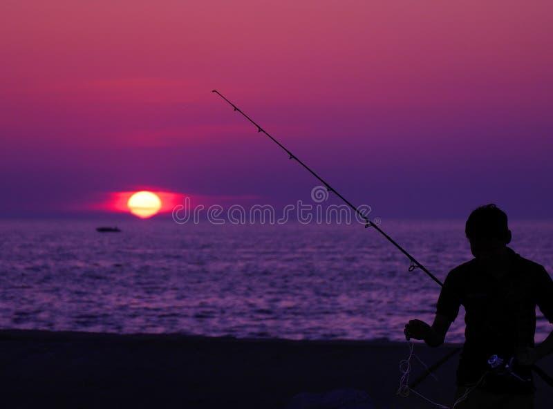 Fiska på solnedgången royaltyfri foto