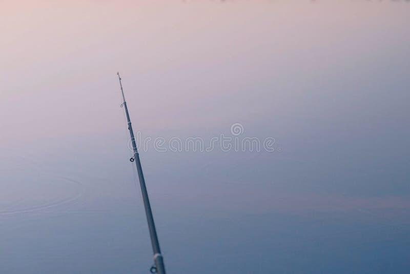 Fiska på solnedgången Metspö över dammet arkivbilder