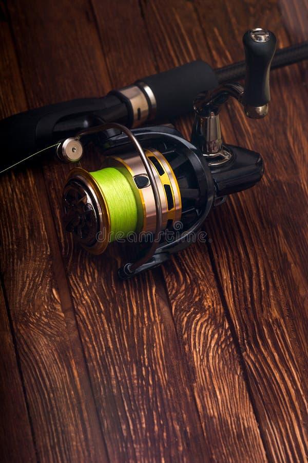 Fiska rullen för en metspö med en grön rev hobby sport spelrum med lampa arkivfoto