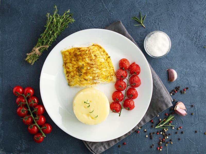Fiska torsk som bakas i ugn med mosade potatisar, tomater, banta sund mat Mörker - grå bakgrund, bästa sikt royaltyfri foto