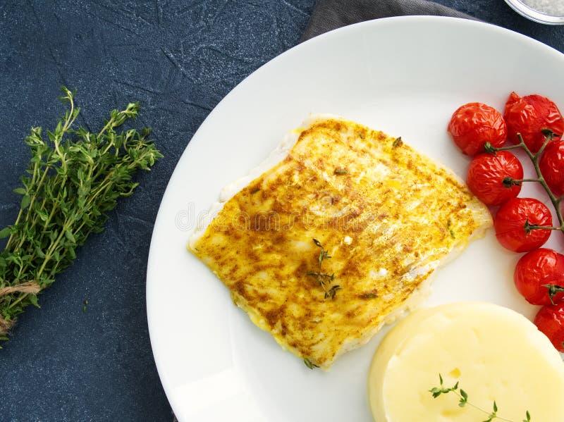 Fiska torsk som bakas i ugn med mosade potatisar, tomater, banta sund mat Mörker - grå bakgrund, bästa sikt royaltyfri bild