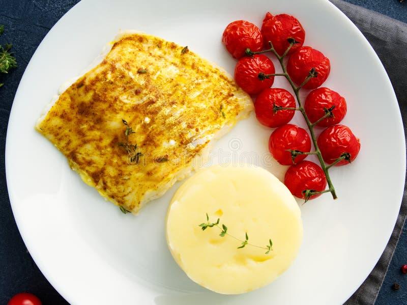 Fiska torsk som bakas i ugn med mosade potatisar, tomater, banta sund mat Mörker - grå bakgrund, bästa sikt arkivbild