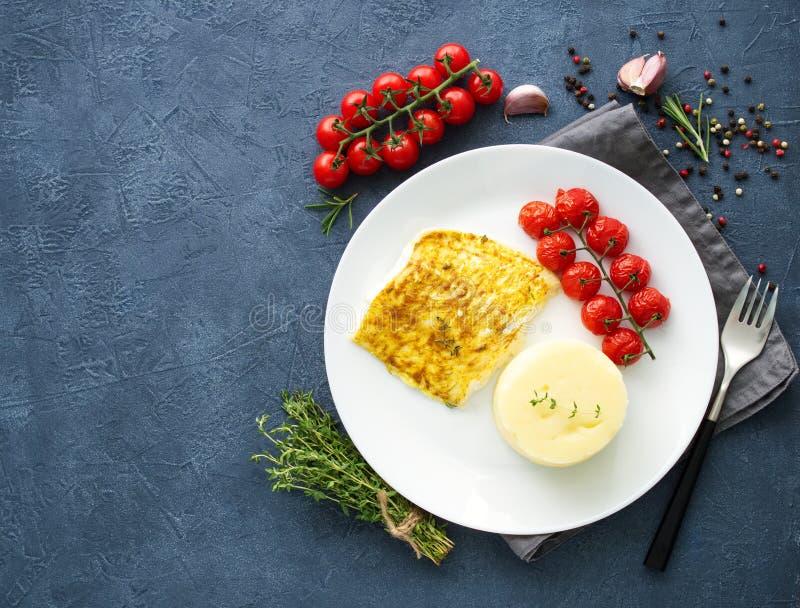 Fiska torsk som bakas i ugn med mosade potatisar, tomater, banta sund mat Mörker - grå bakgrund, bästa sikt, kopieringsutrymme arkivfoton