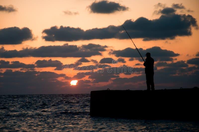Fiska under solnedgång på Alexandria i Egypten royaltyfria foton