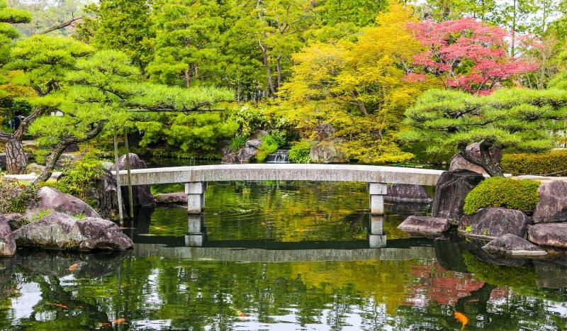 Fiskar det trädgårds- dammet för zenen med bron och karpen i Japan arkivbilder
