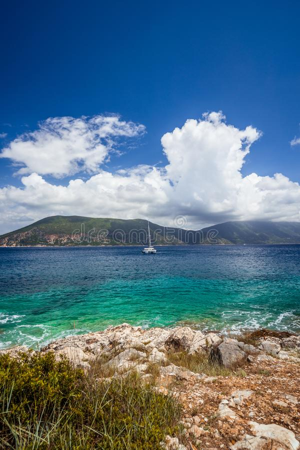 Fiskardo town, crystal clear transparent blue turquoise teal Mediterranean sea water. White yacht in open sea at anchor stock image