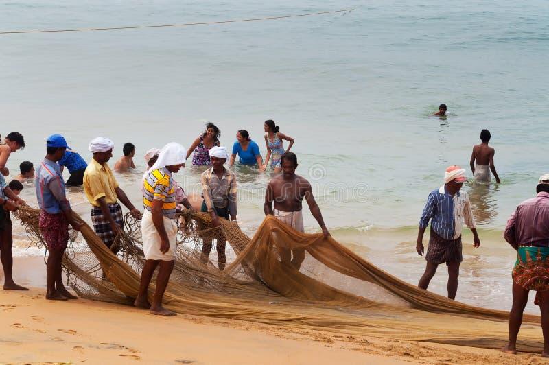 Fiskare är handtag deras fisknät på den Samudra stranden i Kovalam arkivbild