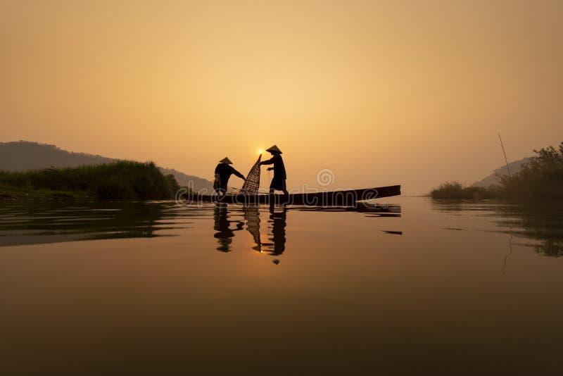 Fiskare arbetar på fiskebåten i Mekong River under i morgonen royaltyfri bild