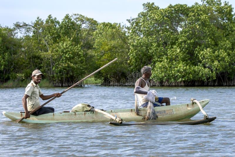 Fiskare att paddla deras utriggarekanot över den Pottuvil lagun royaltyfri fotografi