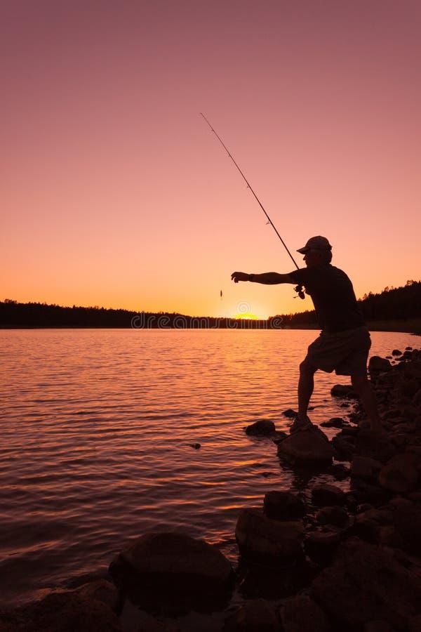 Fiskare Checking Lure på solnedgången arkivbilder