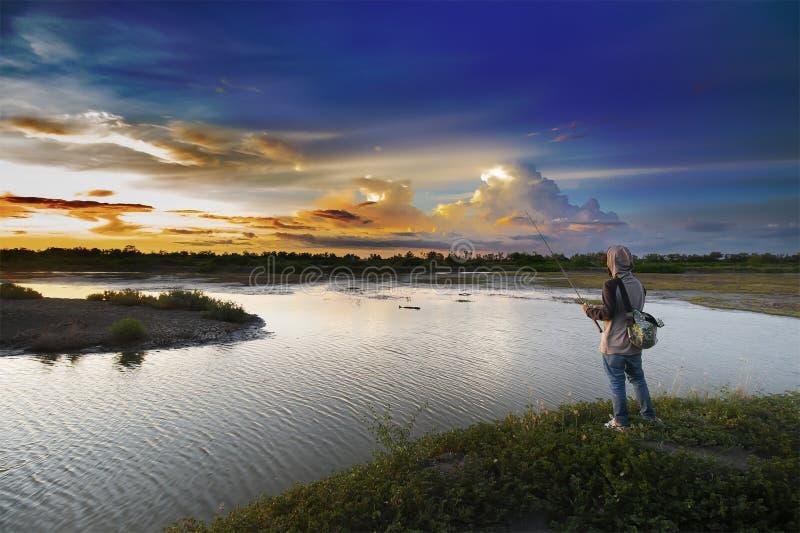 Fiskare fiskar på sjön med en vacker himmel arkivfoton