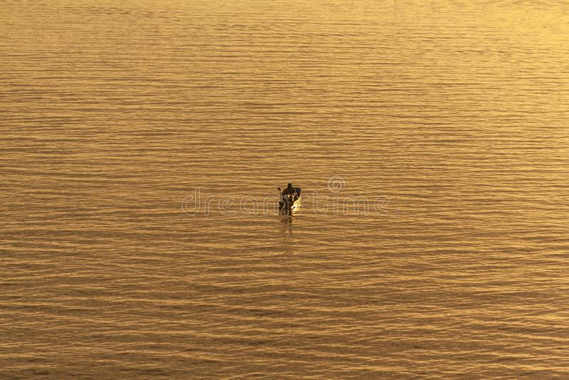 Fiskare i ett fartyg på lugna vatten under soluppgång i Thailand royaltyfria bilder