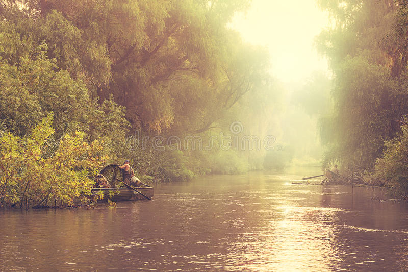 Fiskare i fartyg på den dimmiga floden fotografering för bildbyråer