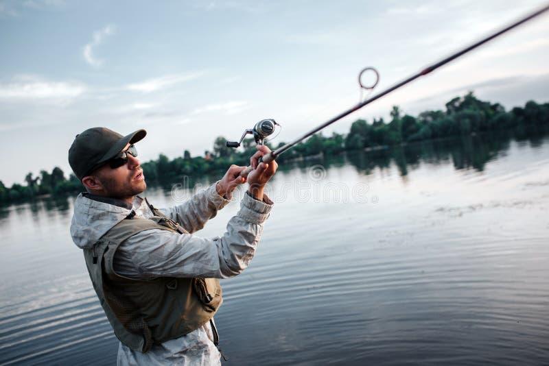 Fiskare i handling Han rymmer witth för den klipska stången båda händer Grabben försöker att fånga laxen Han är allvarlig och kon arkivbilder