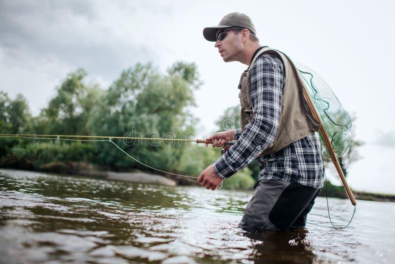 Fiskare i handling Han står i vatten och rymmer den klipska stången i en hand och sked i annan Också har vuxna människan a royaltyfria bilder