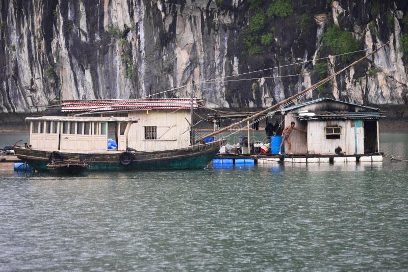 Fiskare i mummel långt fjärd-, fiskfartyg och husfiskare i underbart landskap av den Halong fjärden, Vietnam royaltyfri bild