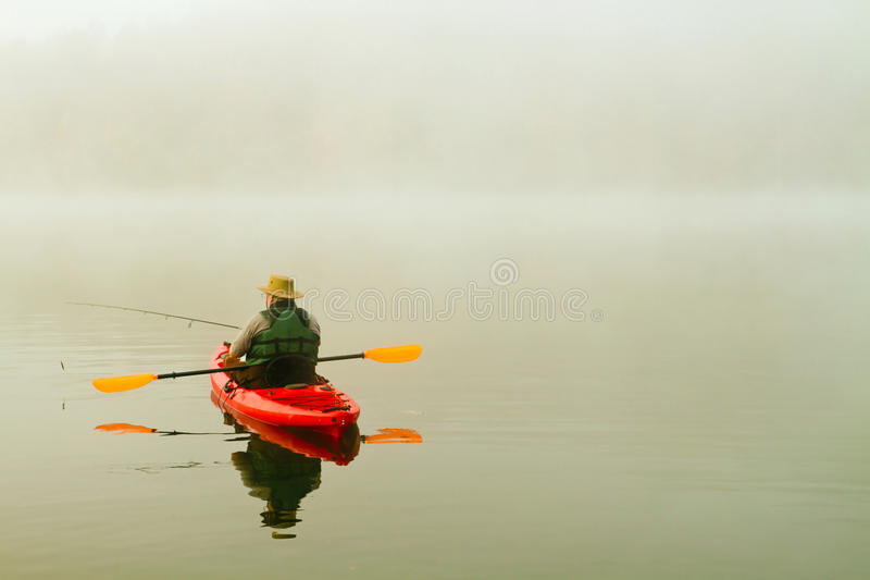 Fiskare i röd kajak arkivfoton