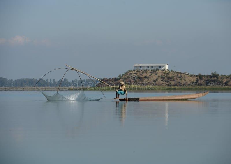 Fiskare i sjön med traditionellt netto på en kanot royaltyfri fotografi