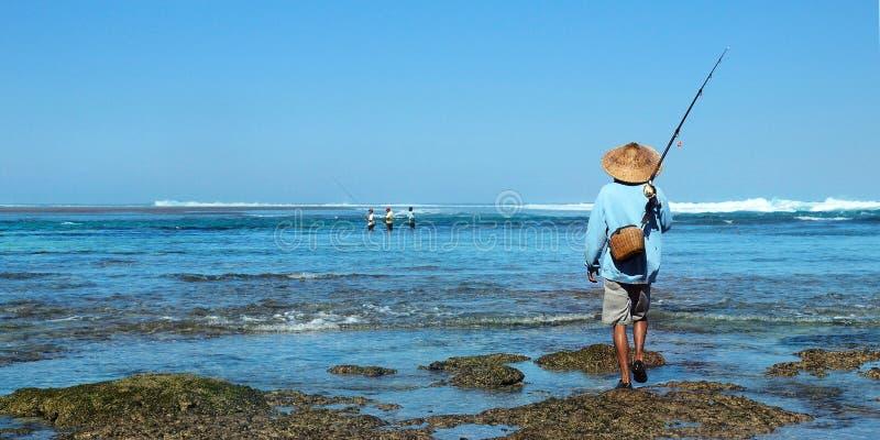 Fiskare med bambuhatten som rymmer hans metspö royaltyfri foto
