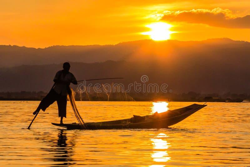 Fiskare med benrodd under solnedgång, inlesjö i Myanmar ( royaltyfria bilder