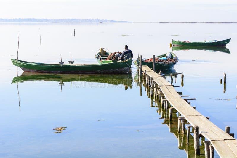 Fiskare med deras forntida fartyg, nedg?ng p? gryning S?der v?stra Sardinia royaltyfri bild