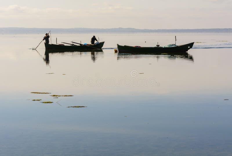 Fiskare med deras forntida fartyg, nedg?ng p? gryning S?der v?stra Sardinia royaltyfri fotografi