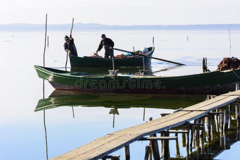 Fiskare med deras forntida fartyg, nedg?ng p? gryning S?der v?stra Sardinia arkivfoto