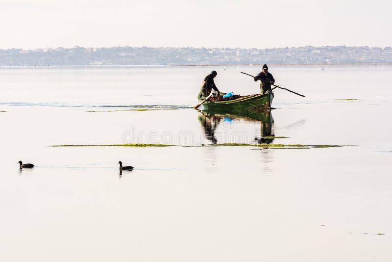 Fiskare med deras forntida fartyg, nedg?ng p? gryning S?der v?stra Sardinia arkivfoton