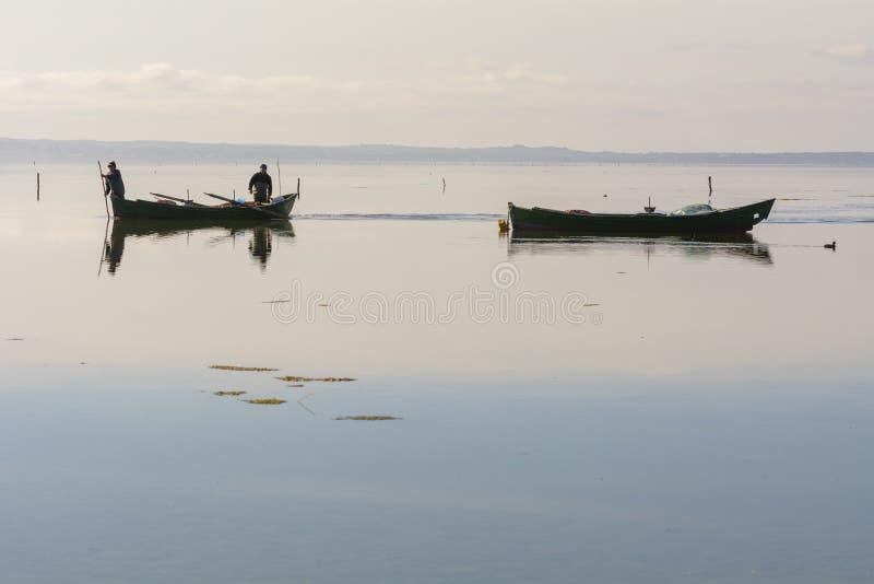 Fiskare med deras forntida fartyg, nedg?ng p? gryning S?der v?stra Sardinia royaltyfria bilder