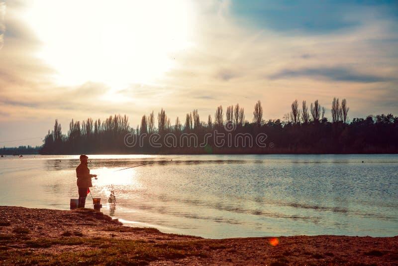 Fiskare med en metspö på flodbanken Härlig sky arkivbilder