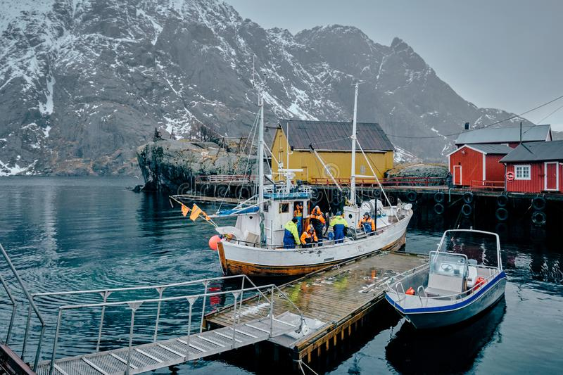 Fiskare och fiskebåt på pir i det Nusfjord fiskeläget, royaltyfria foton