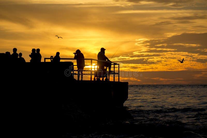 Fiskare och fotograf silhouetted mot en inställningssol royaltyfri bild