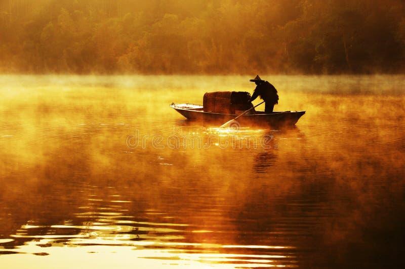 Fiskare och hans fartyg i en dimmig morgon med guld- solljus arkivbilder