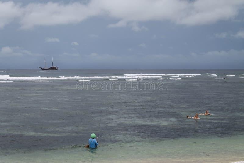 Fiskare och surfare på den Serangan stranden arkivbilder